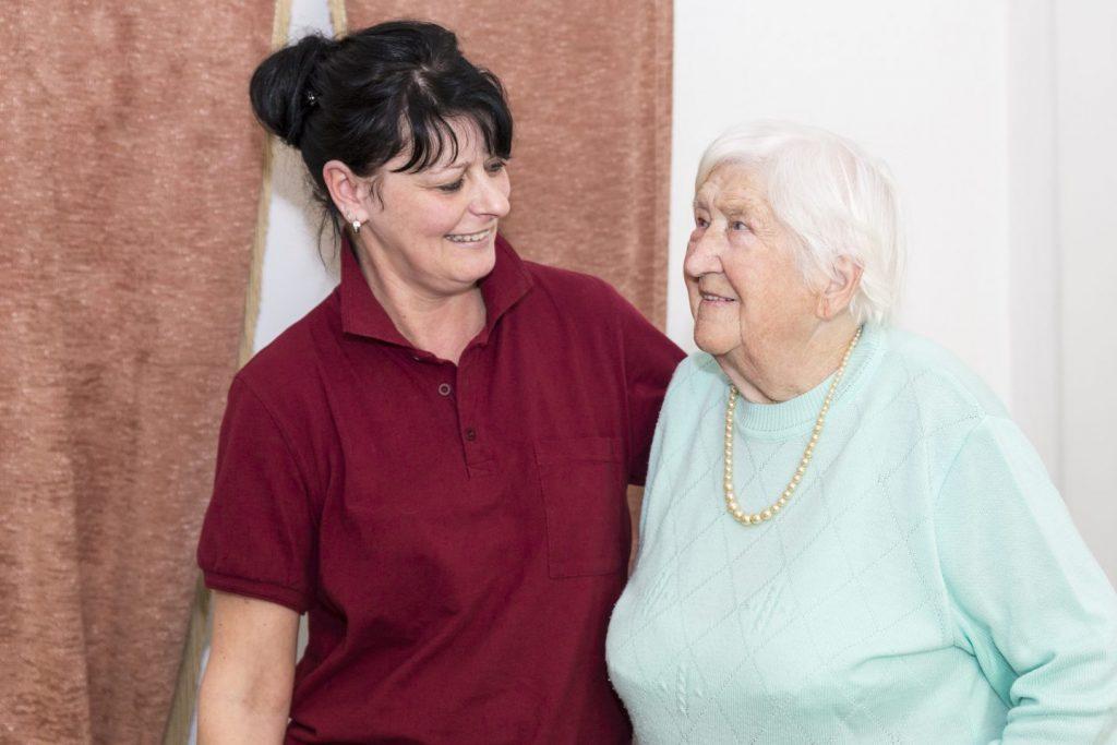 Pflegekraft begrüßt Kundin der Ambulanten Pflege