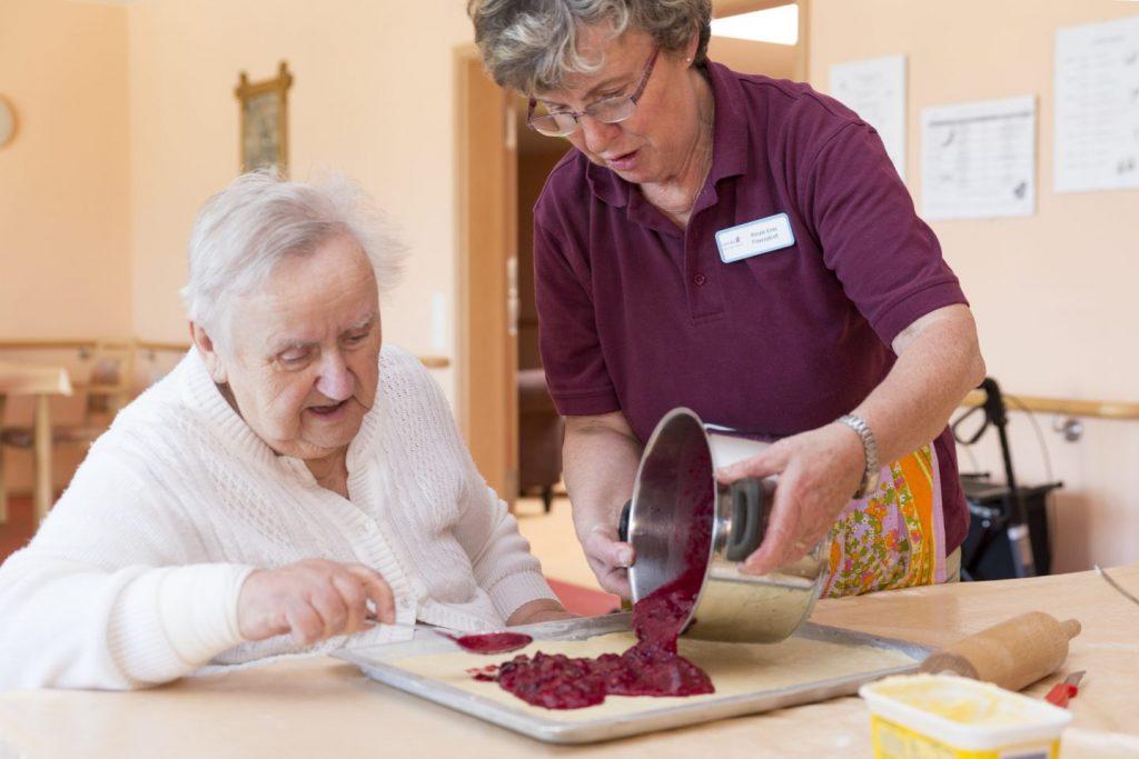 Mitarbeiter backt mit Bewohner einen Kuchen