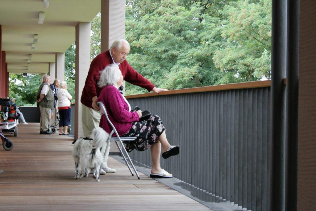 Bewohner der Seniorenwohnanlage schauen vom Balkon in den Garten