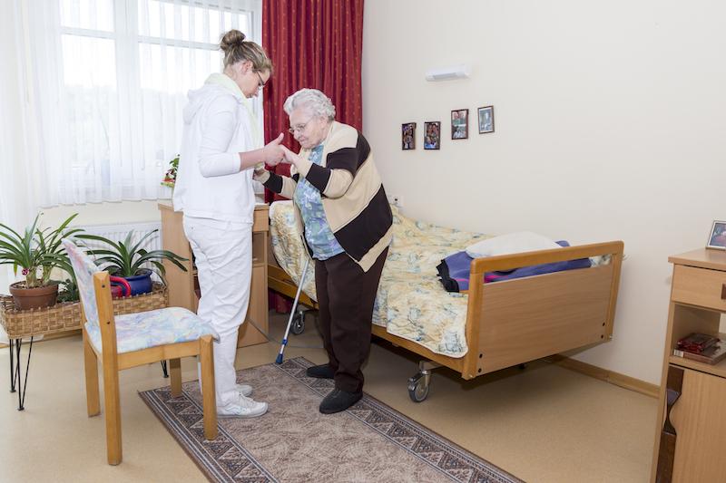 eine junge Pflegekraft hilft einer Bewohnerin aufzustehen